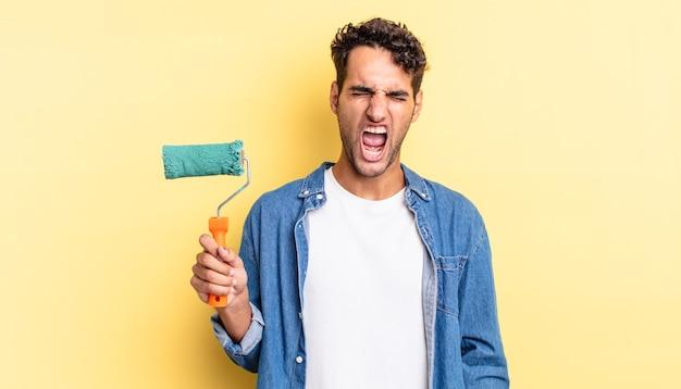 Spaanse knappe man die agressief schreeuwt en er erg boos uitziet. roller verf concept