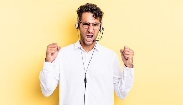 Spaanse knappe man die agressief schreeuwt met een boze uitdrukking. telemarketeer concept