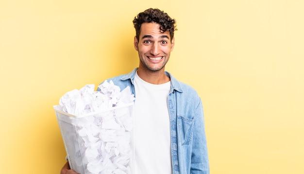 Spaanse knappe man die er blij en aangenaam verrast uitziet. papier ballen prullenbak concept