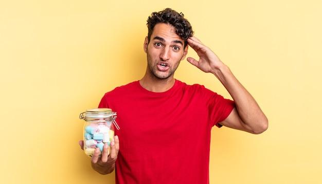 Spaanse knappe man die er blij, verbaasd en verrast uitziet. snoep concept