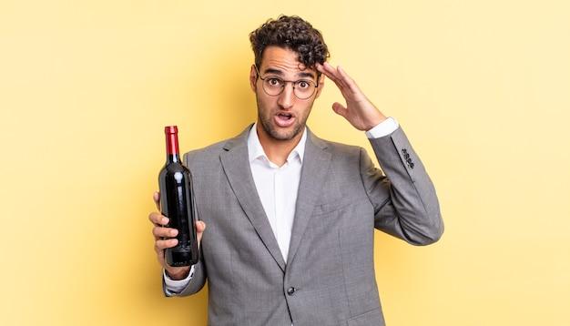 Spaanse knappe man die er blij, verbaasd en verrast uitziet. wijnfles concept