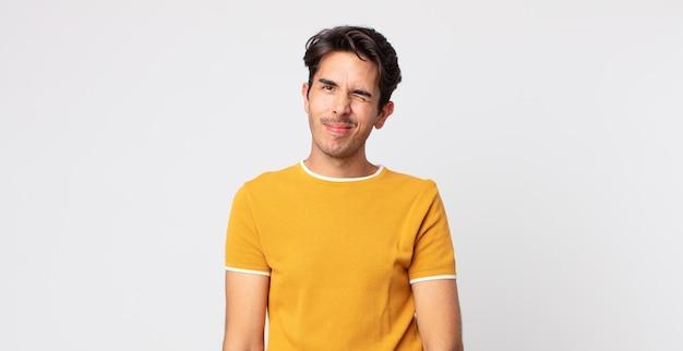 Spaanse knappe man die er gelukkig en vriendelijk uitziet, lacht en je met een positieve houding aankijkt