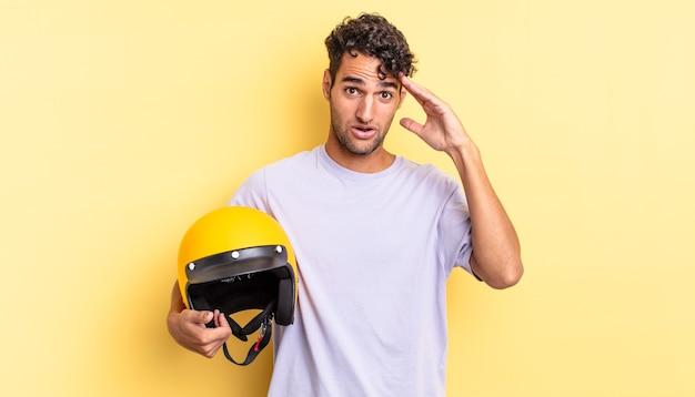 Spaanse knappe man die er gelukkig, verbaasd en verrast uitziet. motorhelm concept