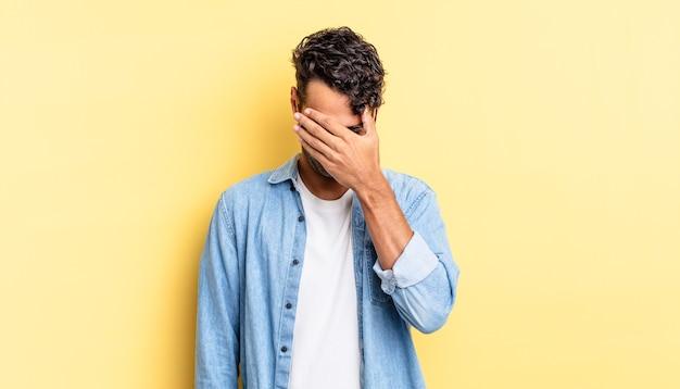 Spaanse knappe man die er gestrest, beschaamd of overstuur uitziet, met hoofdpijn