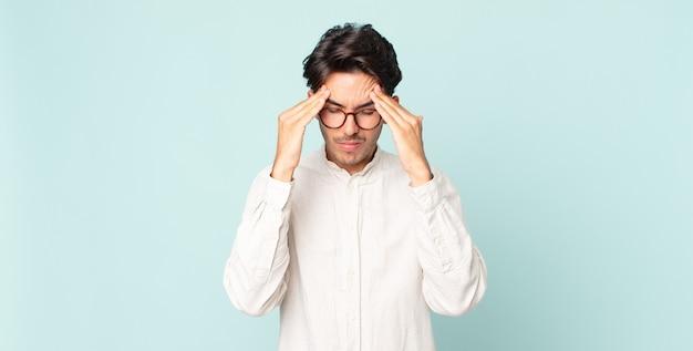 Spaanse knappe man die er gestrest en gefrustreerd uitziet, onder druk werkt met hoofdpijn en last heeft van problemen