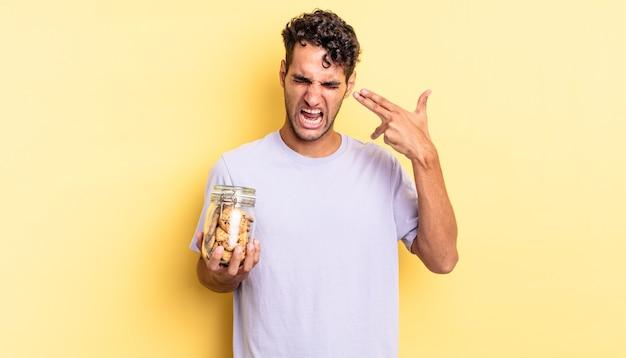 Spaanse knappe man die er ongelukkig en gestrest uitziet, zelfmoordgebaar dat een pistoolteken maakt. koekjes concept