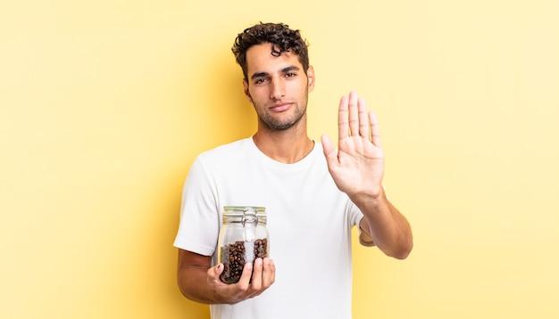 Spaanse knappe man die er serieus uitziet en een open palm toont die een stopgebaar maakt. koffiebonen fles
