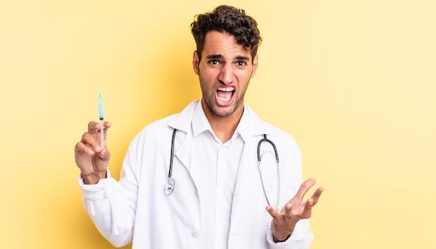 Spaanse knappe man die er wanhopig, gefrustreerd en gestresst uitziet, arts en srynge-concept