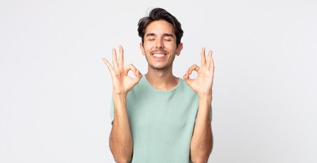 Spaanse knappe man die geconcentreerd en mediterend kijkt, tevreden en ontspannen voelt, denkt of een keuze maakt