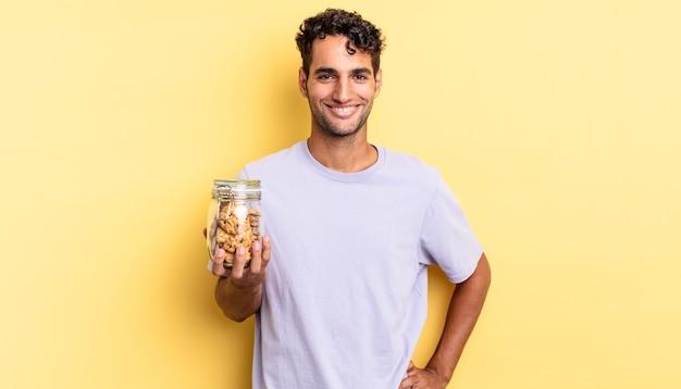 Spaanse knappe man die gelukkig lacht met een hand op de heup en zelfverzekerd. koekjes concept