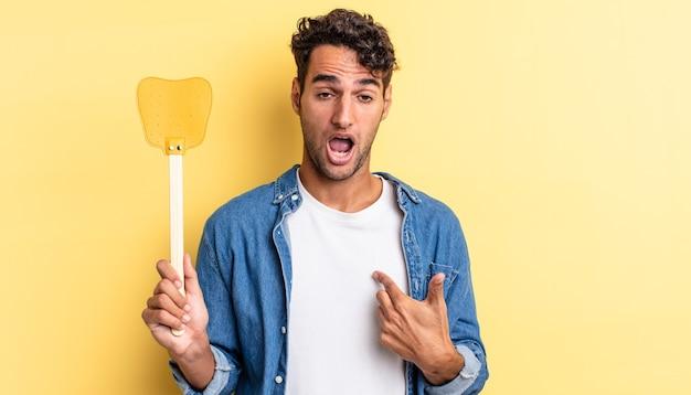 Spaanse knappe man die geschokt en verrast kijkt met wijd open mond, wijzend naar zichzelf. doodt vliegen concept