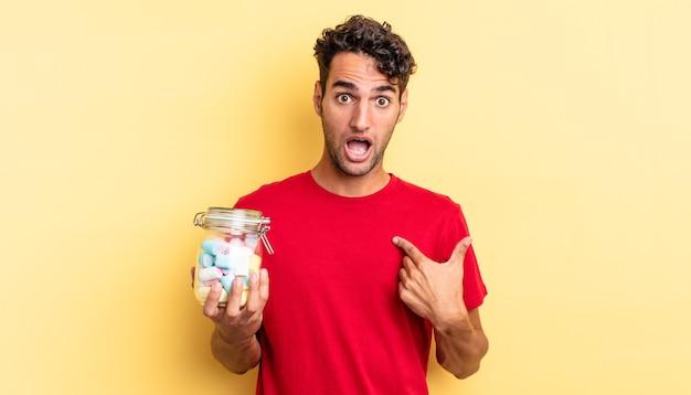 Spaanse knappe man die geschokt en verrast kijkt met wijd open mond, wijzend naar zichzelf. snoep concept