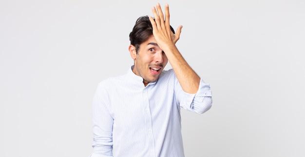 Spaanse knappe man die handpalm naar voorhoofd steekt en denkt oeps, na een domme fout te hebben gemaakt of zich te herinneren, zich dom te voelen