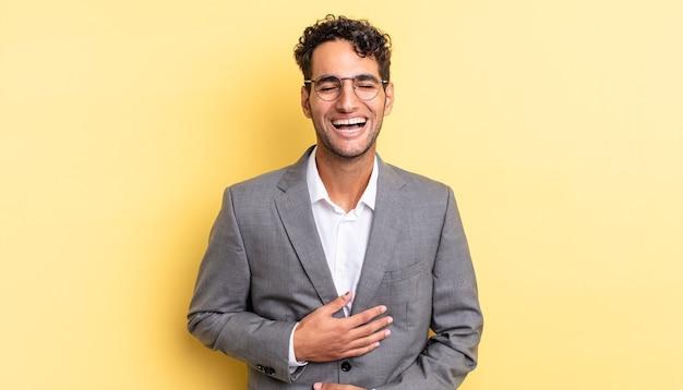 Spaanse knappe man die hardop lacht om een hilarische grap. bedrijfsconcept