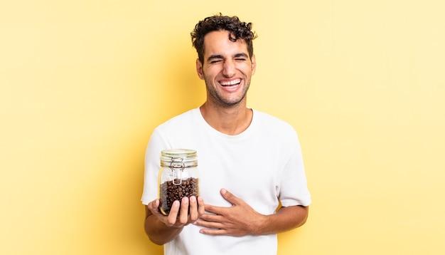 Spaanse knappe man die hardop lacht om een hilarische grap. koffiebonen fles