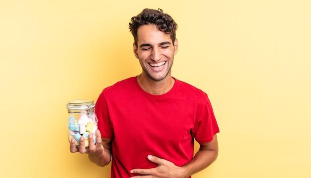 Spaanse knappe man die hardop lacht om een hilarische grap. snoep concept