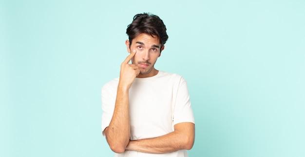 Spaanse knappe man die je in de gaten houdt, niet vertrouwt, kijkt en alert en waakzaam blijft
