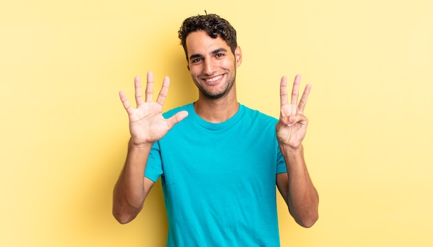 Spaanse knappe man die lacht en er vriendelijk uitziet, met nummer acht