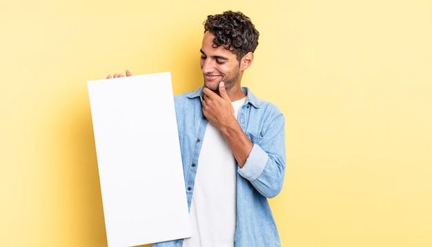 Spaanse knappe man die lacht met een gelukkige, zelfverzekerde uitdrukking met de hand op de kin. leeg canvasconcept