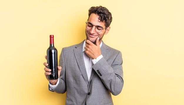 Spaanse knappe man die lacht met een gelukkige, zelfverzekerde uitdrukking met de hand op de kin. wijnfles concept