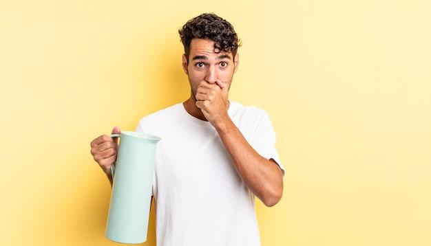 Spaanse knappe man die mond bedekt met handen met een geschokt. koffie thermos concept