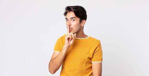 Spaanse knappe man die om stilte en stilte vraagt, met de vinger voor de mond gebarend, shh zegt of een geheim houdt