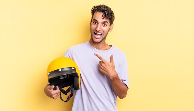 Spaanse knappe man die opgewonden en verrast kijkt en naar de zijkant wijst. motorhelm concept