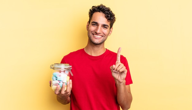 Spaanse knappe man die trots en zelfverzekerd glimlacht en nummer één maakt. snoep concept