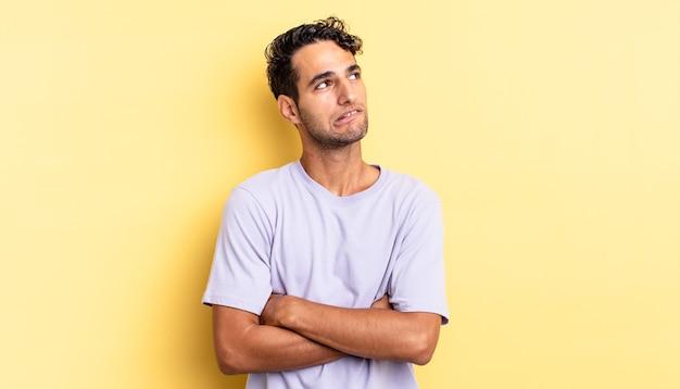 Spaanse knappe man die twijfelt of denkt, lip bijt en zich onzeker voelt