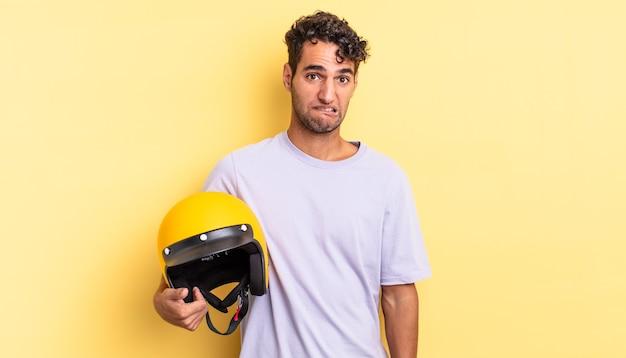 Spaanse knappe man die verbaasd en verward kijkt. motorhelm concept