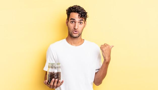Spaanse knappe man die verbaasd kijkt in ongeloof. koffiebonen fles