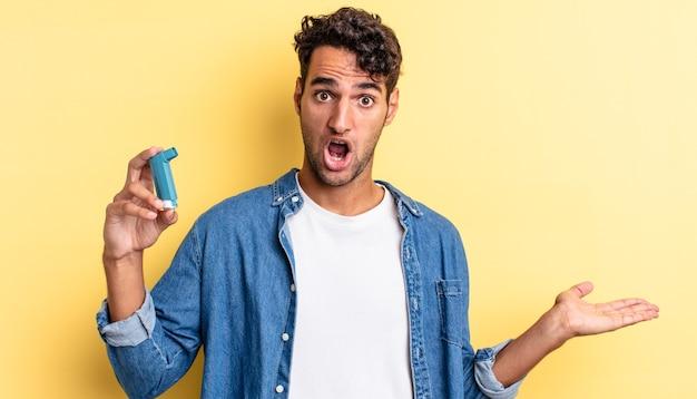 Spaanse knappe man die verrast en geschokt kijkt, met open mond terwijl hij een object vasthoudt. astma concept