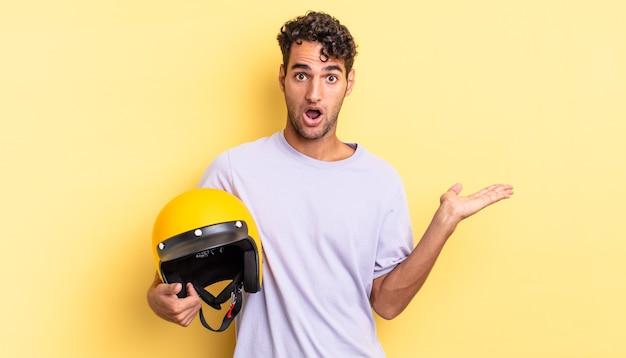Spaanse knappe man die verrast en geschokt kijkt, met open mond terwijl hij een object vasthoudt. motorhelm concept