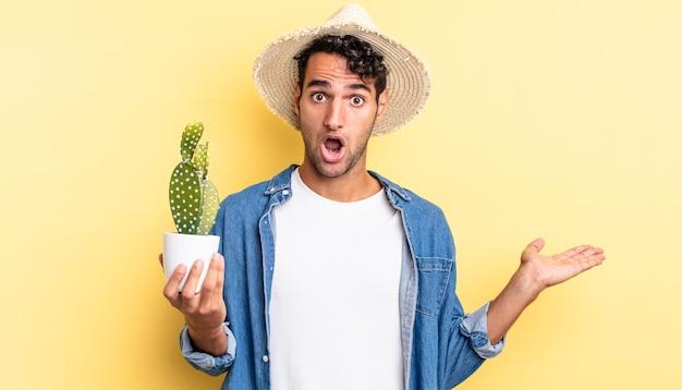 Spaanse knappe man die verrast en geschokt kijkt, met open mond terwijl hij een objectboer en een cactusconcept vasthoudt