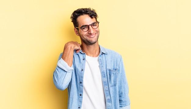 Spaanse knappe man die vrolijk en zelfverzekerd lacht met een vriendelijke glimlach