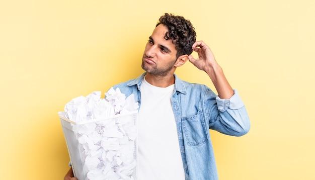 Spaanse knappe man die vrolijk lacht en dagdroomt of twijfelt. papier ballen prullenbak concept