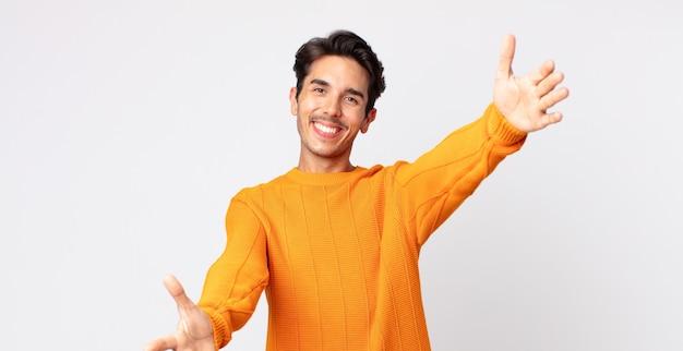 Spaanse knappe man die vrolijk lacht en een warme, vriendelijke, liefdevolle welkomstknuffel geeft, zich gelukkig en schattig voelt