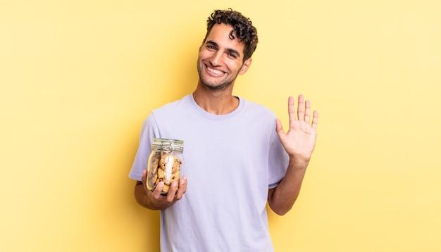 Spaanse knappe man die vrolijk lacht, met de hand zwaait, je verwelkomt en begroet. koekjes concept