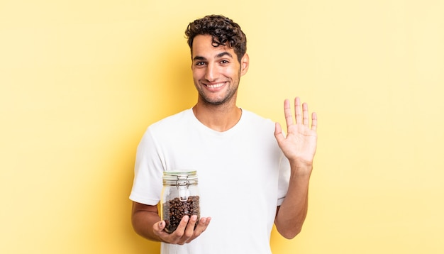 Spaanse knappe man die vrolijk lacht, met de hand zwaait, je verwelkomt en begroet. koffiebonen fles