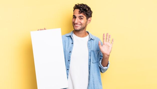 Spaanse knappe man die vrolijk lacht, met de hand zwaait, je verwelkomt en begroet. leeg canvasconcept