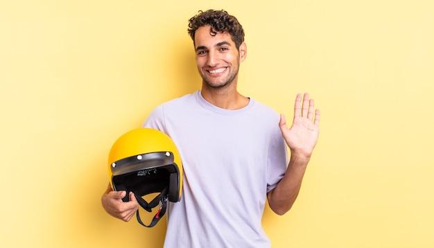 Spaanse knappe man die vrolijk lacht, met de hand zwaait, je verwelkomt en begroet. motorhelm concept