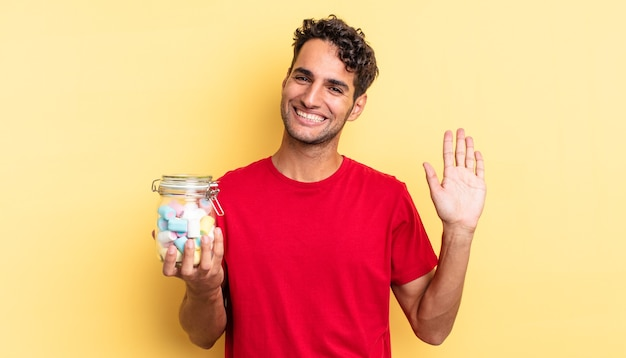 Spaanse knappe man die vrolijk lacht, met de hand zwaait, je verwelkomt en begroet. snoep concept