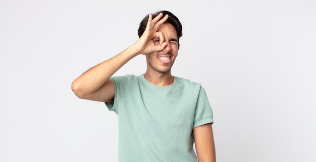 Spaanse knappe man die vrolijk lacht met een grappig gezicht, een grapje maakt en door een kijkgaatje kijkt, geheimen bespioneert