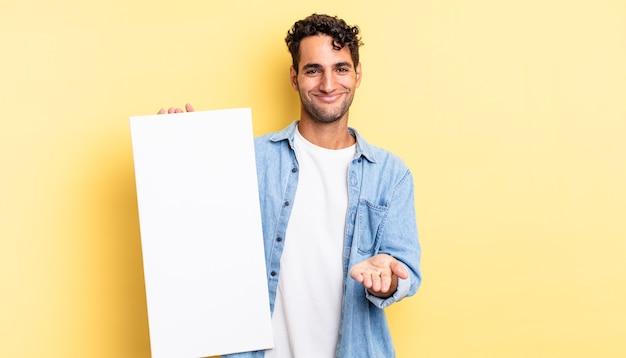 Spaanse knappe man die vrolijk lacht met vriendelijk en een concept aanbiedt en toont. leeg canvasconcept