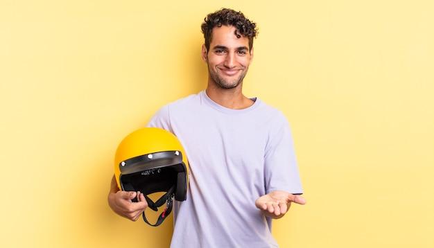 Spaanse knappe man die vrolijk lacht met vriendelijk en een concept aanbiedt en toont. motorhelm concept