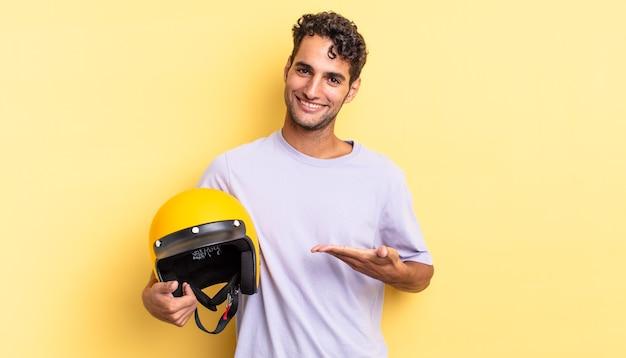 Spaanse knappe man die vrolijk lacht, zich gelukkig voelt en een concept toont. motorhelm concept