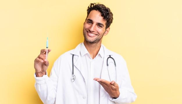 Spaanse knappe man die vrolijk lacht, zich gelukkig voelt en een conceptarts en een srynge-concept toont