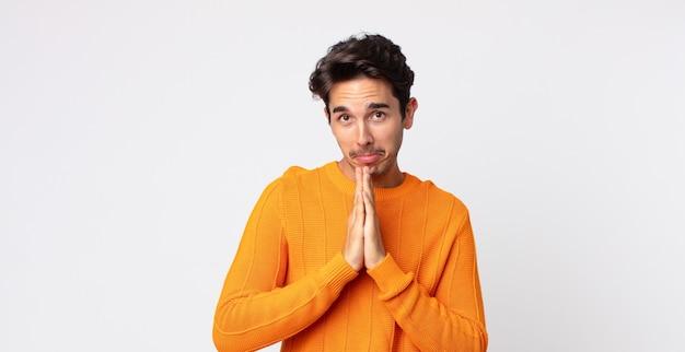 Spaanse knappe man die zich bezorgd, hoopvol en religieus voelt, trouw bidt met ingedrukte handpalmen, smekend om vergiffenis
