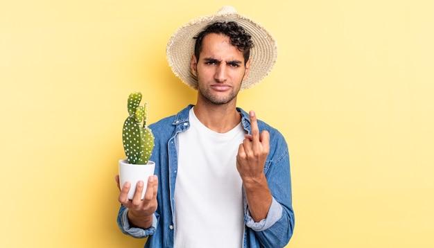 Spaanse knappe man die zich boos, geïrriteerd, opstandig en agressief boer- en cactusconcept voelt
