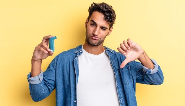 Spaanse knappe man die zich boos voelt en duimen naar beneden laat zien. astma concept